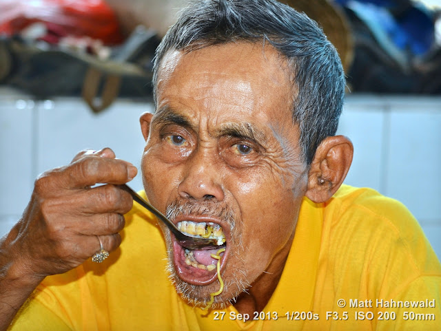 Matt Hahnewald; Facing the World; Asia; people; noodles; street portrait; closeup; eating; slurping; food; travel; travel destination; Indonesia; Indo mee; fried noodles; market; bad teeth; West Kalimantan; Sintang; old man; spoon; eye contact; Nikon DSLR D3100; 50 mm prime lens