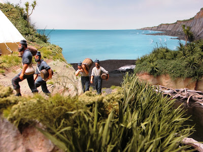 Diorama of 19th-century soldiers moving supplies from the beach up to an encampment.