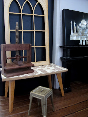 Modern dolls' house miniature room corner with a vintage table, metal stool, book press and wooden window frame propped against the wall on the table.