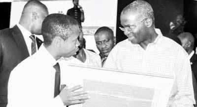Mr Babatunde Fashola receiving his pencil drawing from a Nigerian youth, Obinna Onyenali
