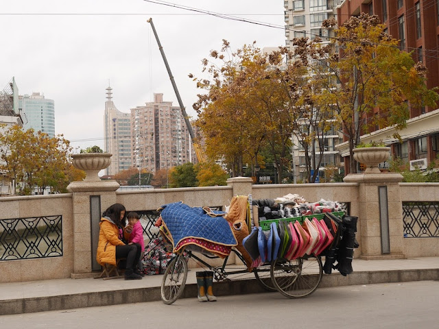 woman sitting with a child next to a tricycle cart filled and covered with items for sale in Shanghai