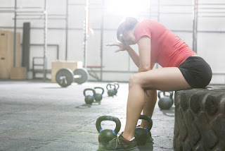 A woman at the gym struggles to finish her workout. She is exhausted and unmotivated.