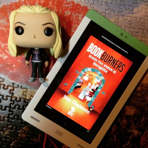 A Funko Pop of Rose Tyler lies beside a white Kobo with the cover of Bookburners Season Two, Episode Six on its screen. The red cover features a stylized illustration of a woman in a blue dress browsing a market.