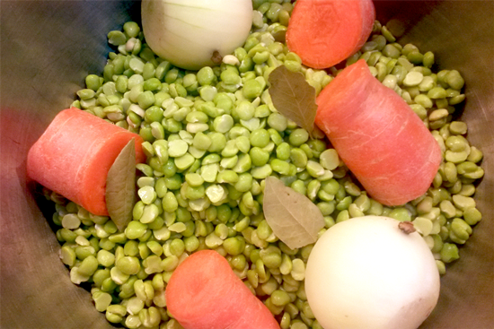 Split peas, vegetables and herbs in a pan about to be boiled.