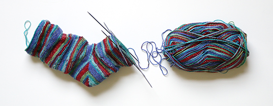 Partially Knit Sock and Skein of Yarn