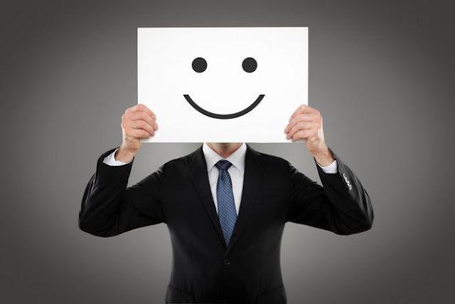hombre en traje formal con un cartel de una cara feliz