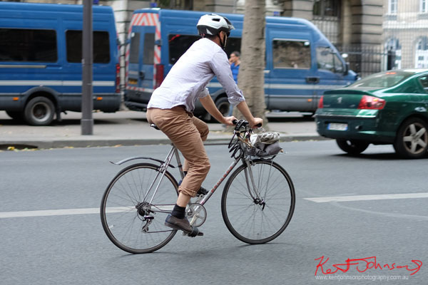 Man in bike helmet riding a vintage silver Peugeot road bike with handlebar basket. Paris photos by Kent Johnson for Street Fashion Sydney.