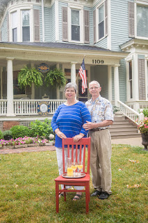 Couple standing behind a red chair with a tray or orange juice on the seat, in front of a Victorian home with hanging ferns and American flag