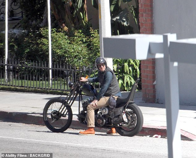 David Beckham looks cool as he takes his beloved motorcycle for a spin on the streets of Los Angeles