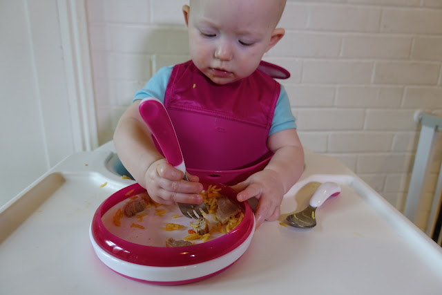 A baby using a fork and plate eating rice