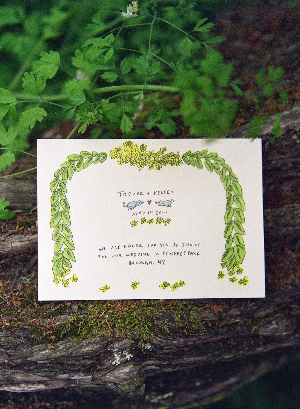 Hand drawn and hand lettered wedding invitation with laurel leaf, yellow flowers and two blue birds
