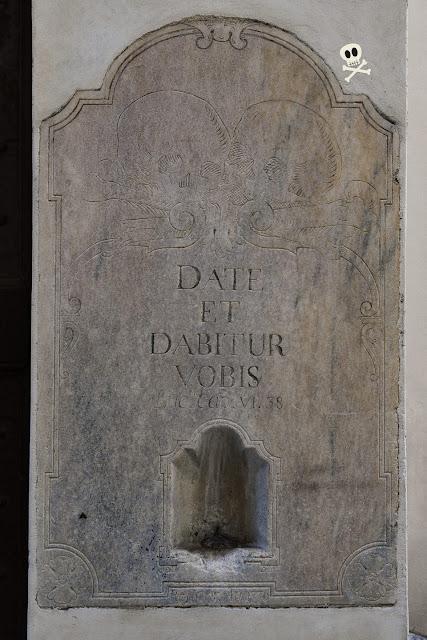 Antiguo limosnero de mármol, con grabado de calaveras y cita bíblica junto a la fecha de restauración del edificio.