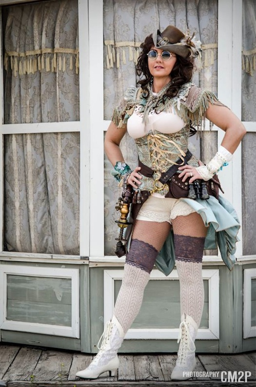 woman wearing sexy steampunk costume in blue and white with hat, corset, bolero, bracer, bloomers, skirt like an old west (western) showgirl