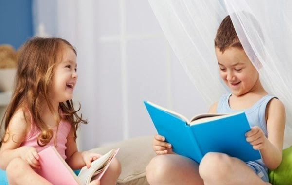 Happy siblings enjoying reading with each other