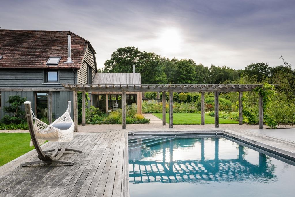 piscina, tarima madera y hamaca de madera