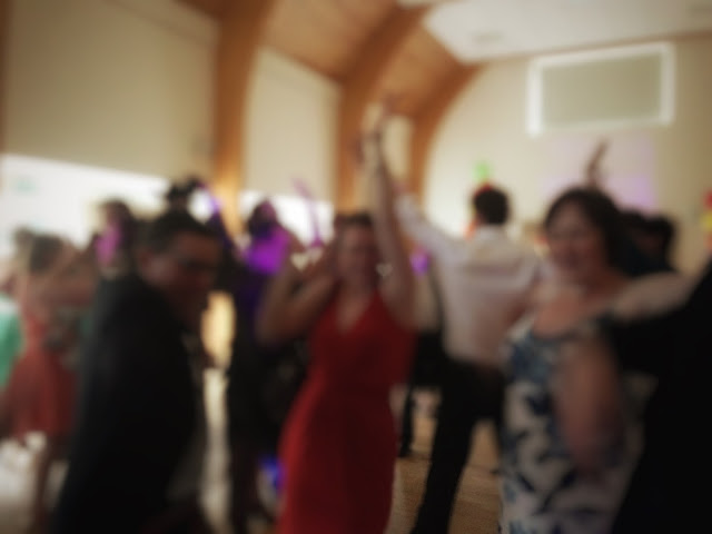 A blurred photo of people dancing in a hall at a wedding