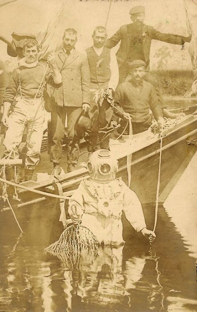 Sponge diver and five men on a boat, Tarpon Springs, Florida.  Real photo postcard,  1907.