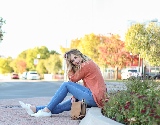 girl sitting on curb wearing orange free people sweater