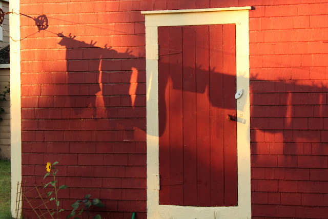Red barn with white trim and the shadow of clothes on a clothesline