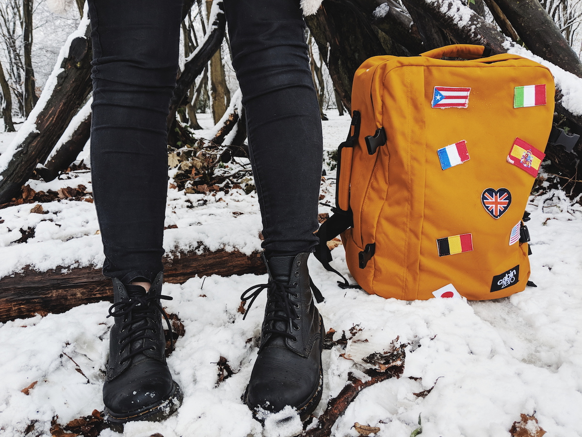 Black Dr. Marten's boots stood next to the Cabin Zero rucksack, which is adorned with flag patches
