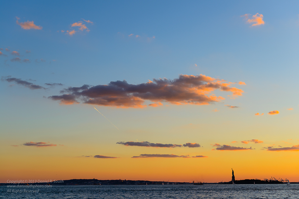 a photo of the statue of liberty at sunset