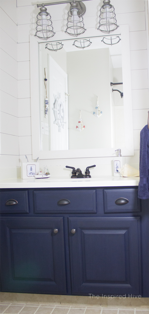 Nautical bathroom makeover with navy blue cabinets