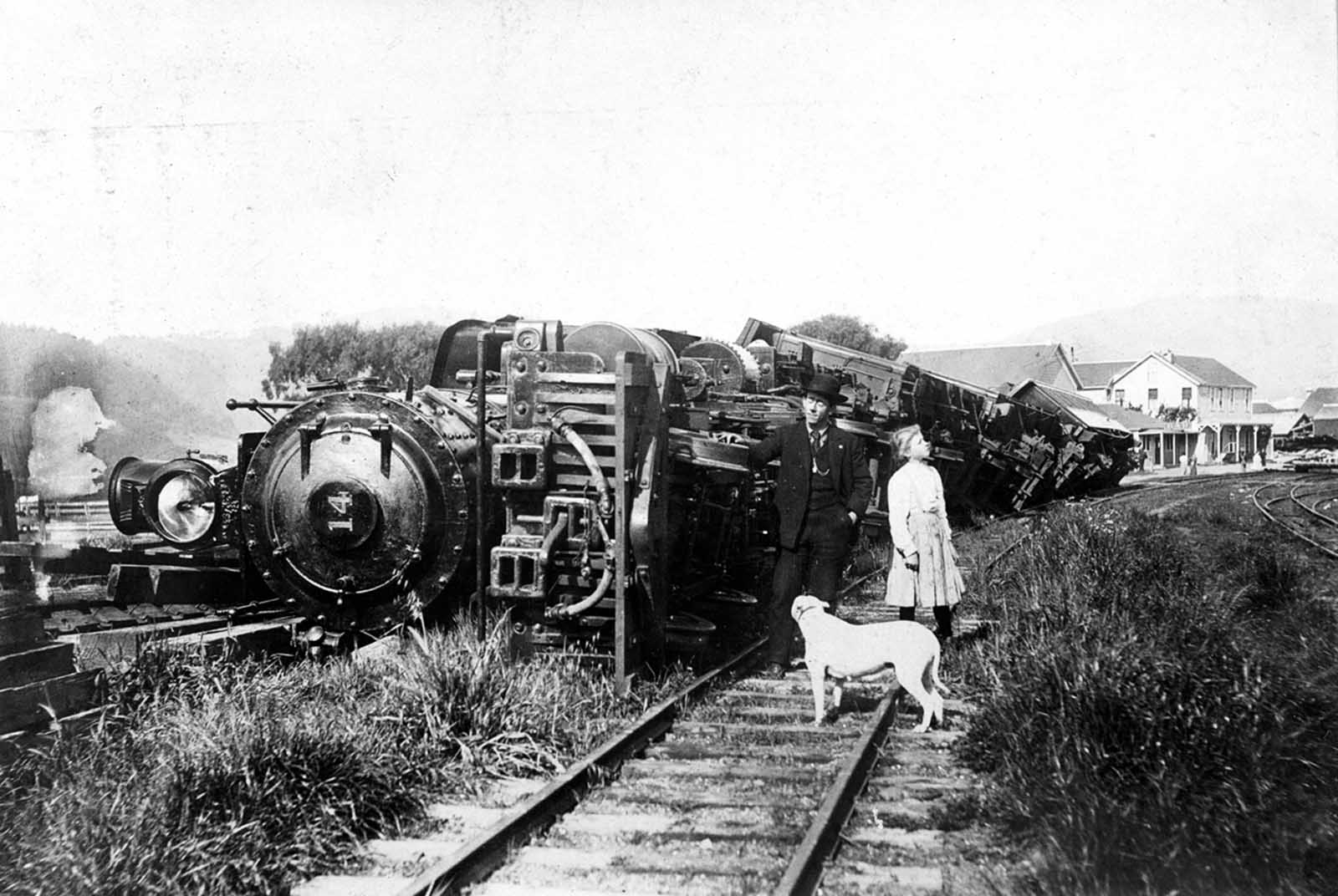 A train thrown down by the earthquake at Point Reyes Station. The train was standing on a siding. Beyond are the buildings of the Point Reyes Hotel and, on the extreme right, the ruin of a stone store which was shaken down.