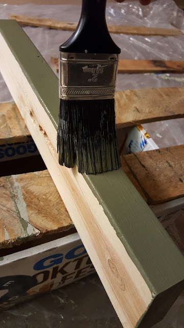 paintbrush applying dark green paint to the edge of a 2x4