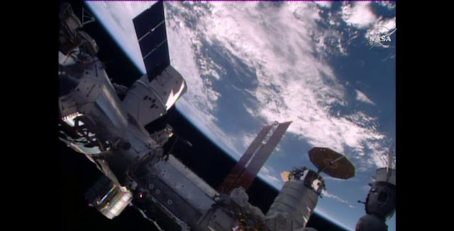 The SpaceX Dragon is seen shortly after it was mated to the Harmony module. The Cygnus cargo craft with its circular solar arrays and the Soyuz TMA-19M spacecraft (bottom right) are also seen in this view. Credit: NASA TV