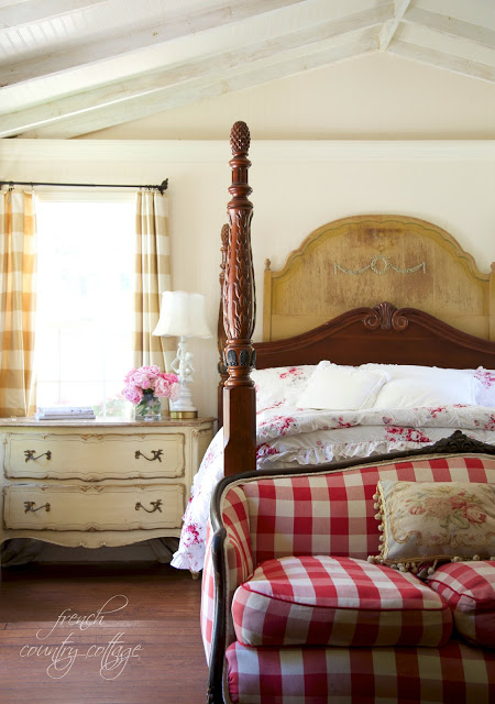 Bedroom with red check sofa and floral bedding