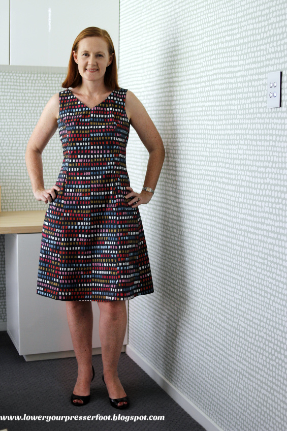 woman modelling a sleeveless summer dress in multi colours