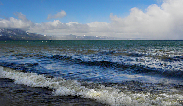 Lake with waves coming in and snowy mountains and clouds in background