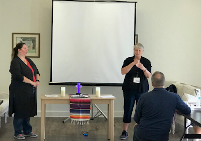 During the SEJ of The UMCD business meeting, Betty Ostrom, the new spiritual advisor of the SEJ board, standing next to the altar, prays for the new board, while Mary Ann Deters (board president) looks on, and Rev. Yates (voice) interprets the prayer.