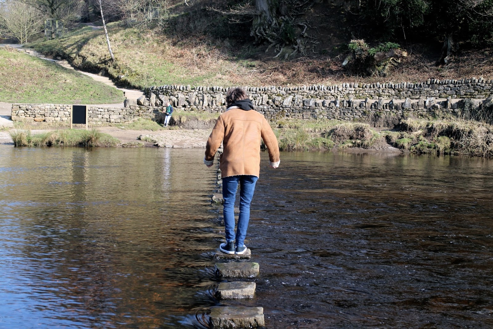 Using the stepping stones to get across the river at Bolton Abbey