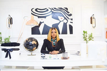 Chioma ikokwu sitting with poise in black suite jacket, blond fringe hair, scarf around her neck. The room decorated with a beautiful two female pattern paints