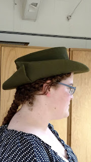 Image is a person in profile wearing a round green hat. The hat's edge is curled up on one side, with an asymmetrical brim.