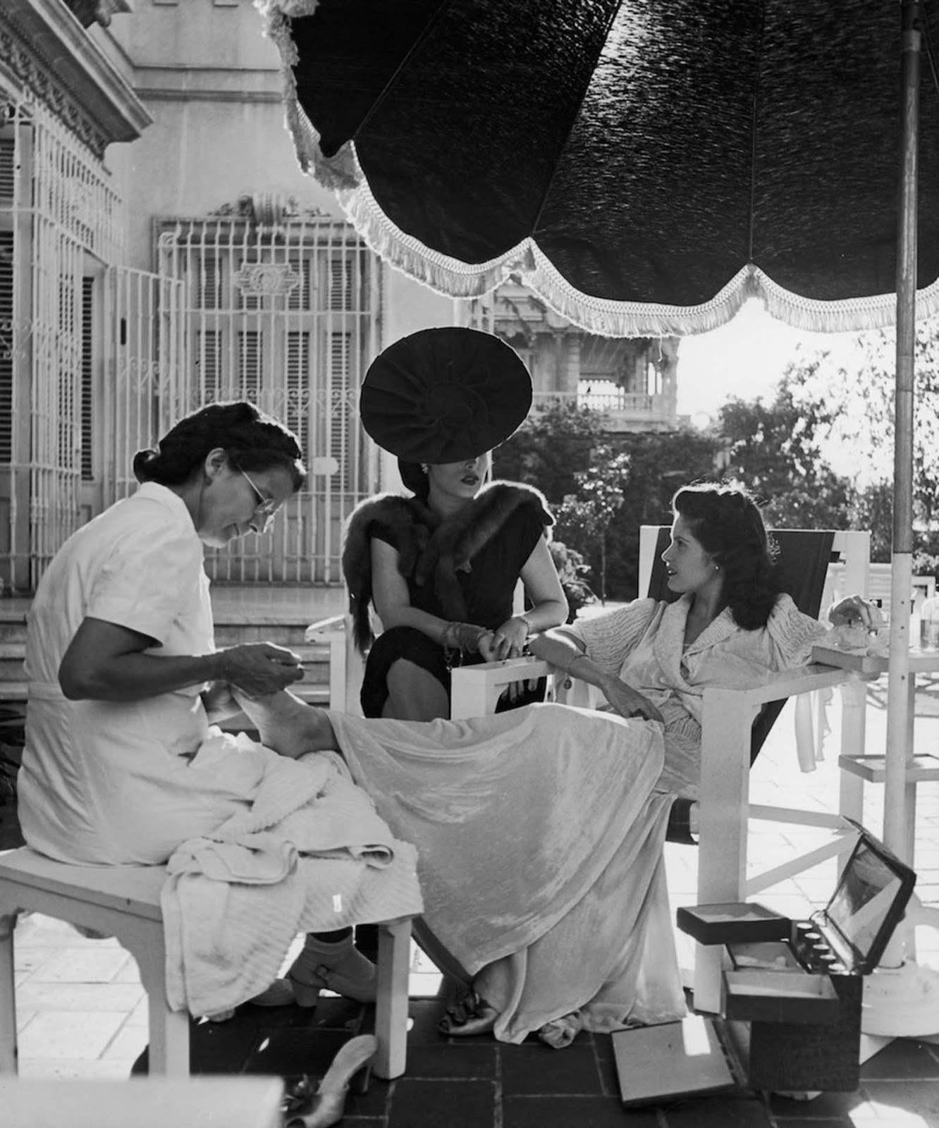 Cuban socialite Aline Johnson gets a pedicure will being visited by her friend Nina Gomez de Freyre. 1946.