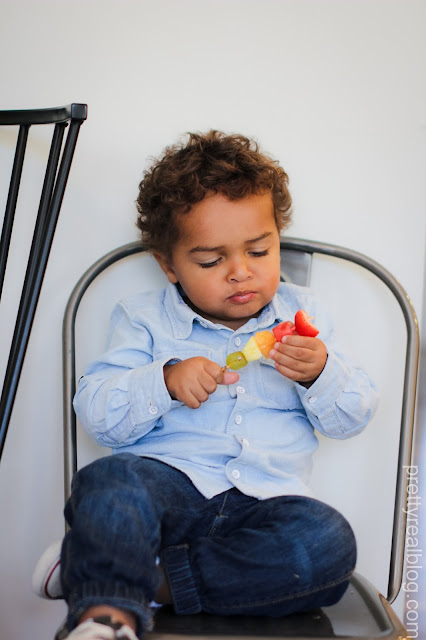 Little boy eating a rainbow fruit skewer