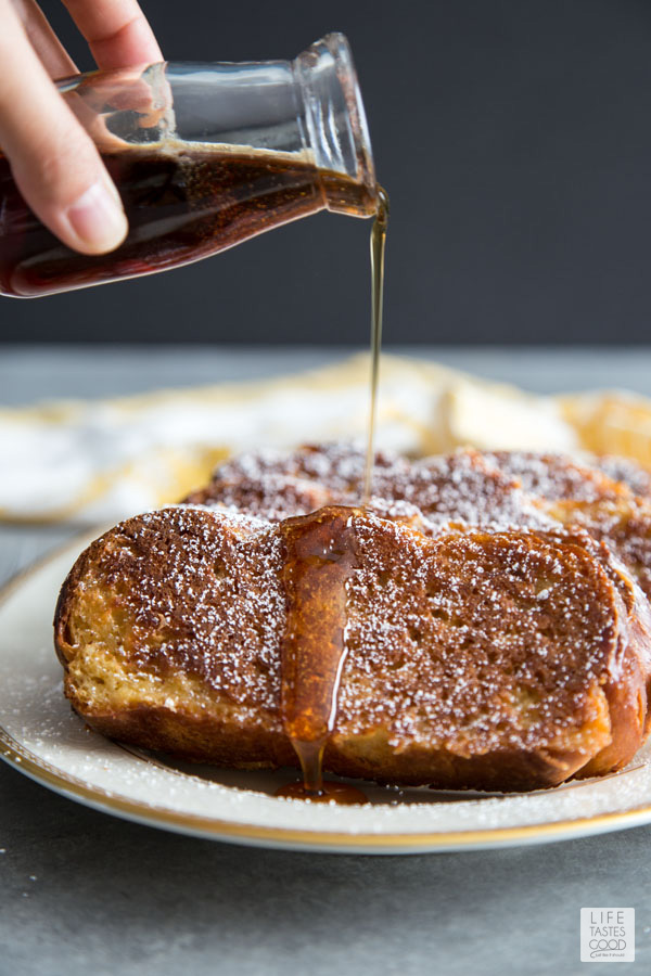 Oven French Toast on a white serving plate topped with powdered sugar and drizzling syrup on top