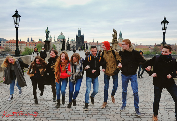 Young people line dancing down the Charles Bridge in Spring. Prague by Travel and Lifestyle Photographer Kent Johnson.