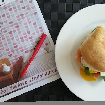 Magazine with a red pen on top of it, next to a plate with a breakfast burger on it.