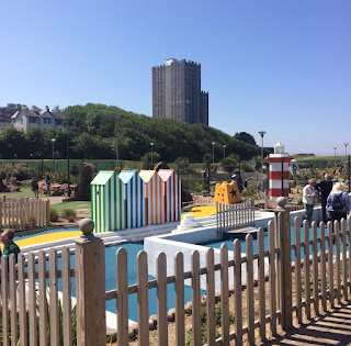 a mini golf course with fake beach huts, fencing, and mini golf course under a blue sky and houses in the background