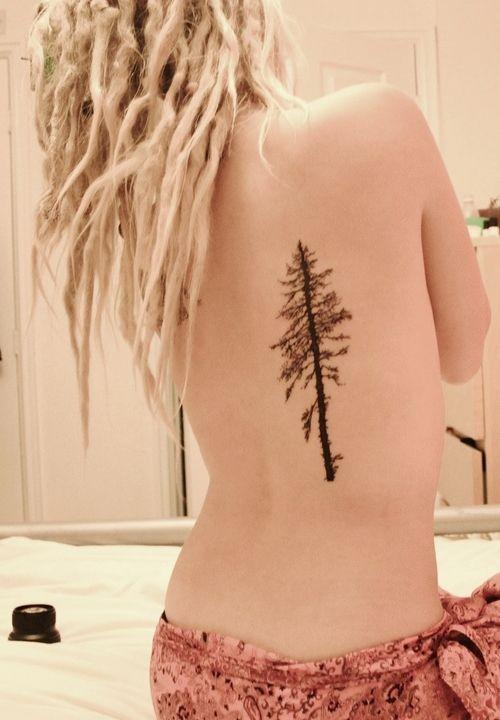 chica con rastas rubias, de espaldas en su cama nos muestra un tatuaje de arbol que lleva en la espalda