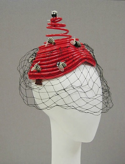 Red toque plastic hat with attached bumblebees and veil on display on mannequin head.