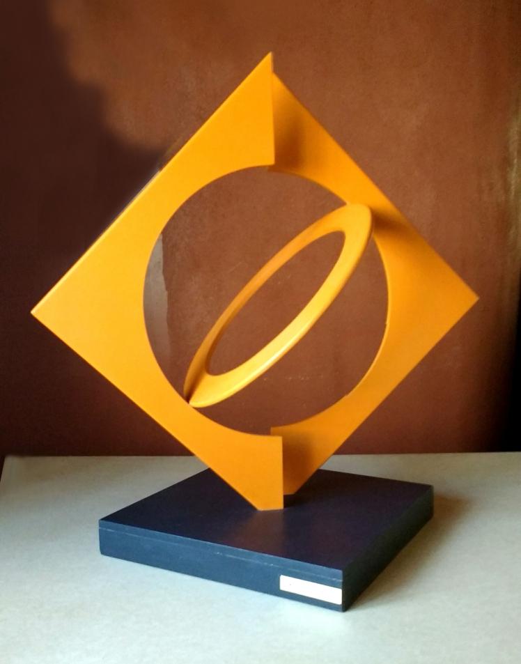 escultura na cor laranja com base preta, em madeira com formas geométricas
