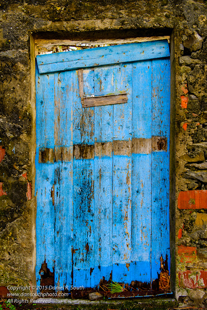 a photo of a blue garden gate in corniglia in the cinque terre coast region of italy
