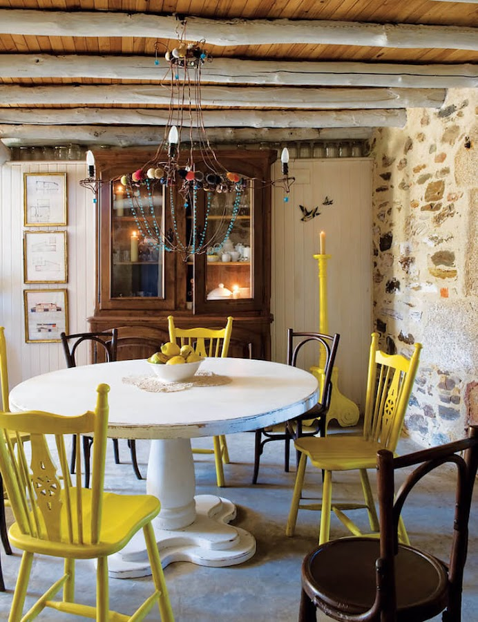 detalle del comedor de una casa rústica con sillas de colores y de fondo una vitrina antigua