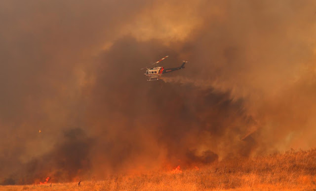 At least 21 dead, hundreds missing as winds fan California wildfires