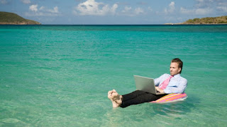An office worker in a clear blue sea, floating on an inflatable chair, and working on a laptop.