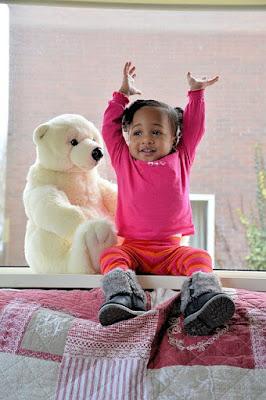 Petite fille amusée levant les bas au ciel, près d'un ours en peluche.